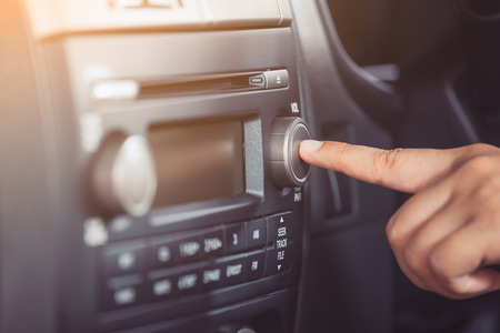Woman hand turn on the radio  while driving a car in vintage color tone