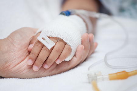 Mother hand holding child hand who have IV solution in the hospital with love and care