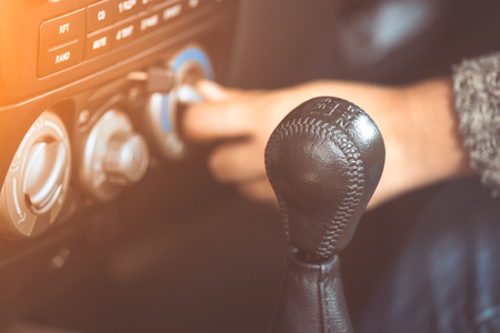 Gear stick for the manual transmission car on driver hand adjusting car air conditioning system in vintage color tone
