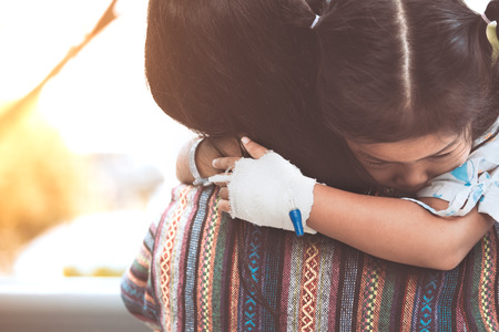 Sick child girl hugging and resting on her mother's shoulder  in the hospital