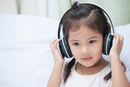 Cute asian child girl in headphones listening the music in her room Reklamní fotografie