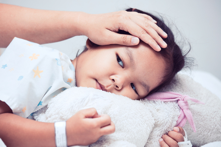 Sick asian child girl is lying in the bed and mother hand touch her forehead with love in the hospital
