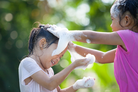 Two happy asian children girl having fun to bath and play with foam together in outside