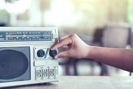 Woman hand adjusting the sound volume on retro radio cassette stereo  in vintage color tone Reklamní fotografie - 83239011
