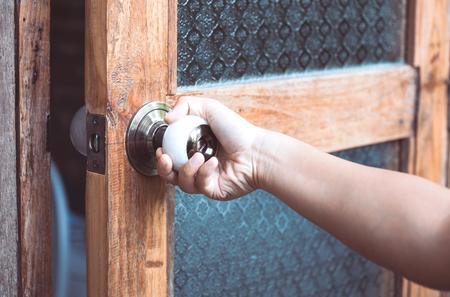 Woman hand opening/closing door knob in vintage style