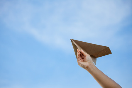Hand holding paper airplane against the sky