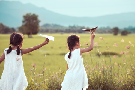 Back view of two asian child girls playing toy paper airplane together in the field in vintage color tone Foto de archivo