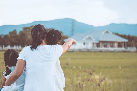 Mother and two asian little child girls looking at beautiful house in the field together in vintage color tone Stock Photo