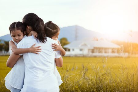 happy asian little girls hugging mother and having fun to play with mother in the field in vintage color tone Stock Photo