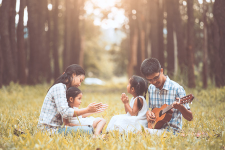 Happy family father playing guitar, mother and two little child girls sing a song, family having fun together in the park at sunset