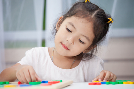 0dfff48ec8b  84107087 - Niña linda que se divierte jugando y aprendiendo alfabetos  magnéticos a bordo en la habitación.