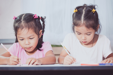 two tone: Two cute asian child girls having fun to draw and paint together in vintage color tone Stock Photo