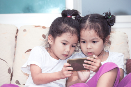 Two cute asian child girls having fun to play game in smartphone together in the room Stock Photo