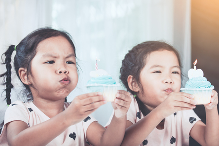 two tone: Two cute asian child girls having fun to  blowing birthday cupcake together in vintage color tone