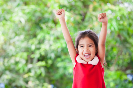 Happy asian child girl in christmas dress raising her hands and shouting with cheerful on green nature background