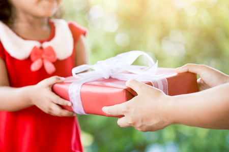 Hands of parent giving Christmas gift to child girl in vintage color tone. Christmas concept. Stock Photo