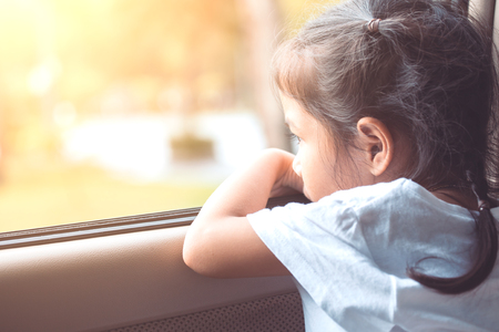 Cute asian little child girl sitting in the car and look out from the car window in the sunset