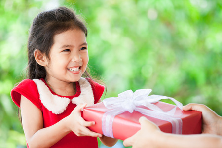Parent giving Christmas gift to cute asian child girl on green nature background. Christmas concept.