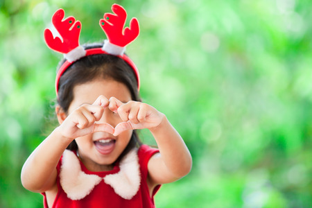 Cute asian child girl in christmas dress making heart shape with hands on green nature background. Love and Christmas concept