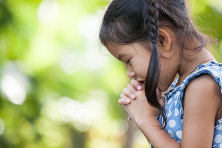 Cute asian little child girl praying with folded her hand for faith,spirituality and religion concept