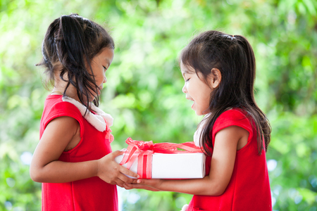 Two cute asian child girls in santa dress holding Christmas gift in hand together on green nature background. Christmas concept.