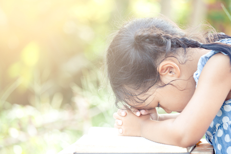 Cute asian little child girl praying with folded her hand on a Holy Bible for faith,spirituality and religion concept in vintage color tone Stock Photo