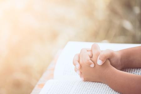 De handen van weinig kindmeisje vouwden in gebed op een Heilige Bijbel voor geloof, spiritualiteit en godsdienstconcept in uitstekende kleurentoon Stockfoto