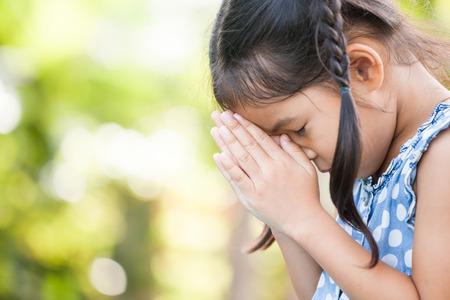 信仰、精神性と宗教の概念のために彼女の手を折って祈るかわいいアジアの小さな子供の女の子