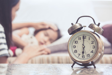 Vintage alarm clock on background of mother taking care asian child girl while she sleeping in the bed
