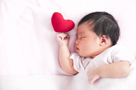 Cute asian newborn baby girl sleeping with red heart in bed
