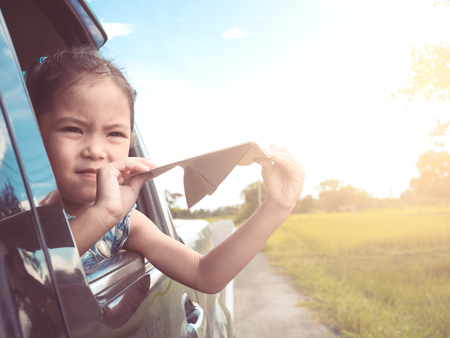 Cute asian little child girl having fun to play with toy paper airplane out of car window in the countryside in vintage color tone