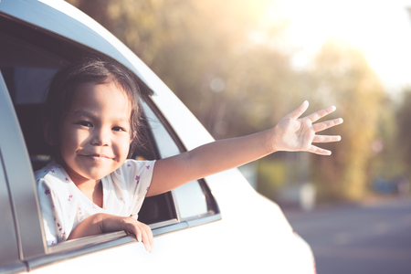 Cute asian little child girl smiling and having fun to  travel by car. Child reach out her hand and look out from car window in the countryside in vintage color tone