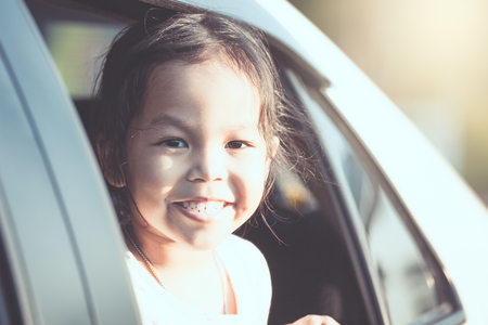 Cute asian little child girl smiling and having fun to  travel by car and looking out from car window in the countryside in vintage color tone