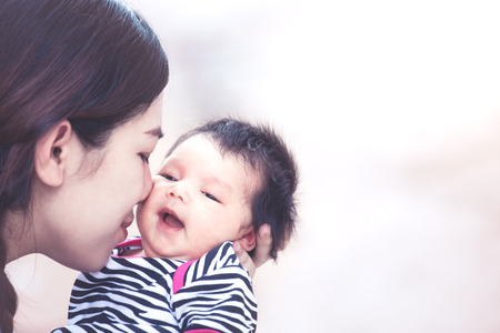 Young asian mother hugging and kissing her newborn baby girl with love in vintage color tone Stock fotó