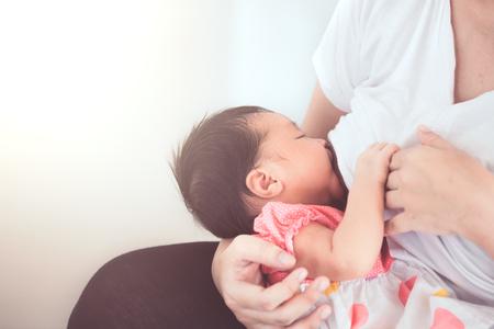 그녀의 신생아 아기 소녀 모유 수유 어머니. 아기는 어머니의 가슴에서 우유를 마시는 동안 행복합니다. 빈티지 색조입니다.