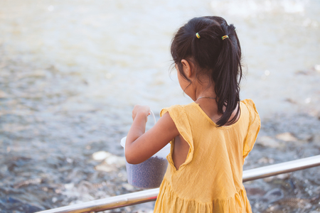 Cute asian little child girl having fun to feed and give food to fish in the pond Stock Photo