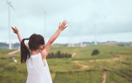 Back view of little asian child girl raise her arms looking at wind turbine field with freshness in vintage color tone Standard-Bild