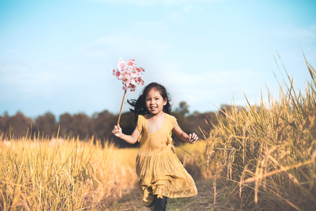 run way: Cute asian little child girl playing with wind turbine and running in the cornfield in vintage color tone