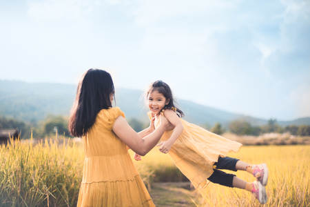 Cute asian child girl smile and fun while mother holding her kid and spinning around in the cornfield in vintage color tone Archivio Fotografico