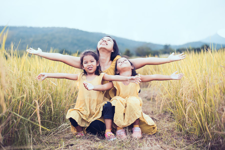 Happy asian little child girls having fun to play with mother and raise thier hand with freshness together in the paddy field in vintage color tone