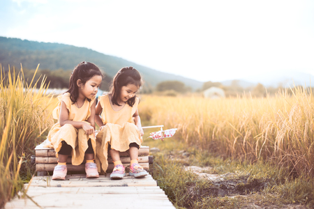 Two happy asian little child girls having fun to play together and sitting on bamboo walkway in the paddy field in vintage color tone Stock Photo