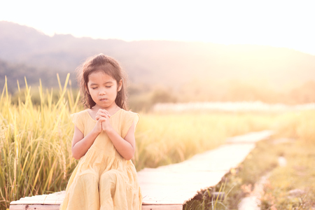 Cute asian little child girl praying with folded her hand and sitting on bamboo walkway in the paddy field in vintage color tone Foto de archivo