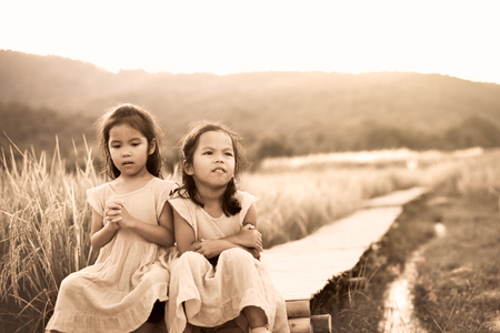 Two asian little child girls who feel bored and sad sitting on bamboo walkway in paddy field in vintage color tone