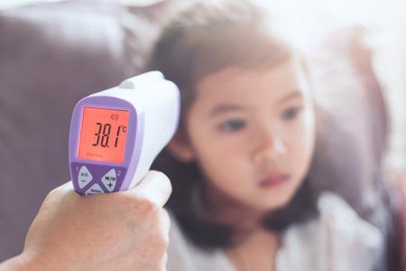 mère mesurer la température de sa petite fille asiatique enfant malade avec thermomètre à l & # 39 ; écoute