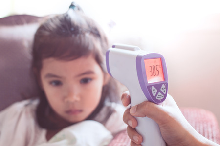Mother measuring temperature her sick asian little child girl with infrared thermometer