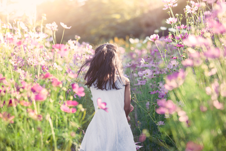 Happy asian little child girl running and having fun in the cosmos flower field in vintage color tone