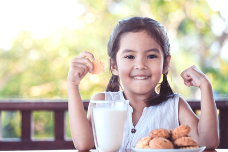 Cute asian little child girl making strong hand while drinking a milk for breakfast with fun
