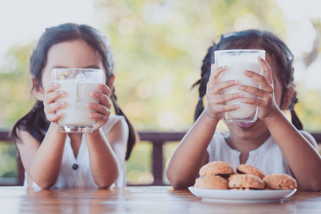 Two cute asian little child girls holding glass of milk for breakfast together with happiness