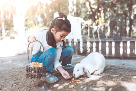 Leuk Aziatisch klein kindmeisje die pret met echt konijn in het landbouwbedrijf hebben te voeden en te spelen Stockfoto