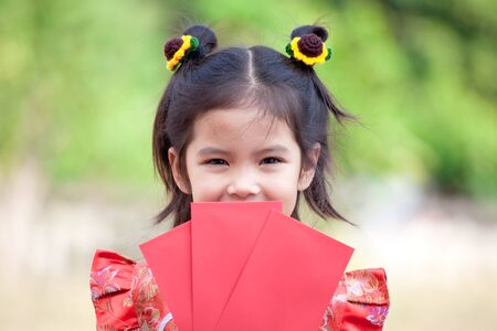 Cute asian child girl holding red envelope and wishing you a happy in Chinese New Year
